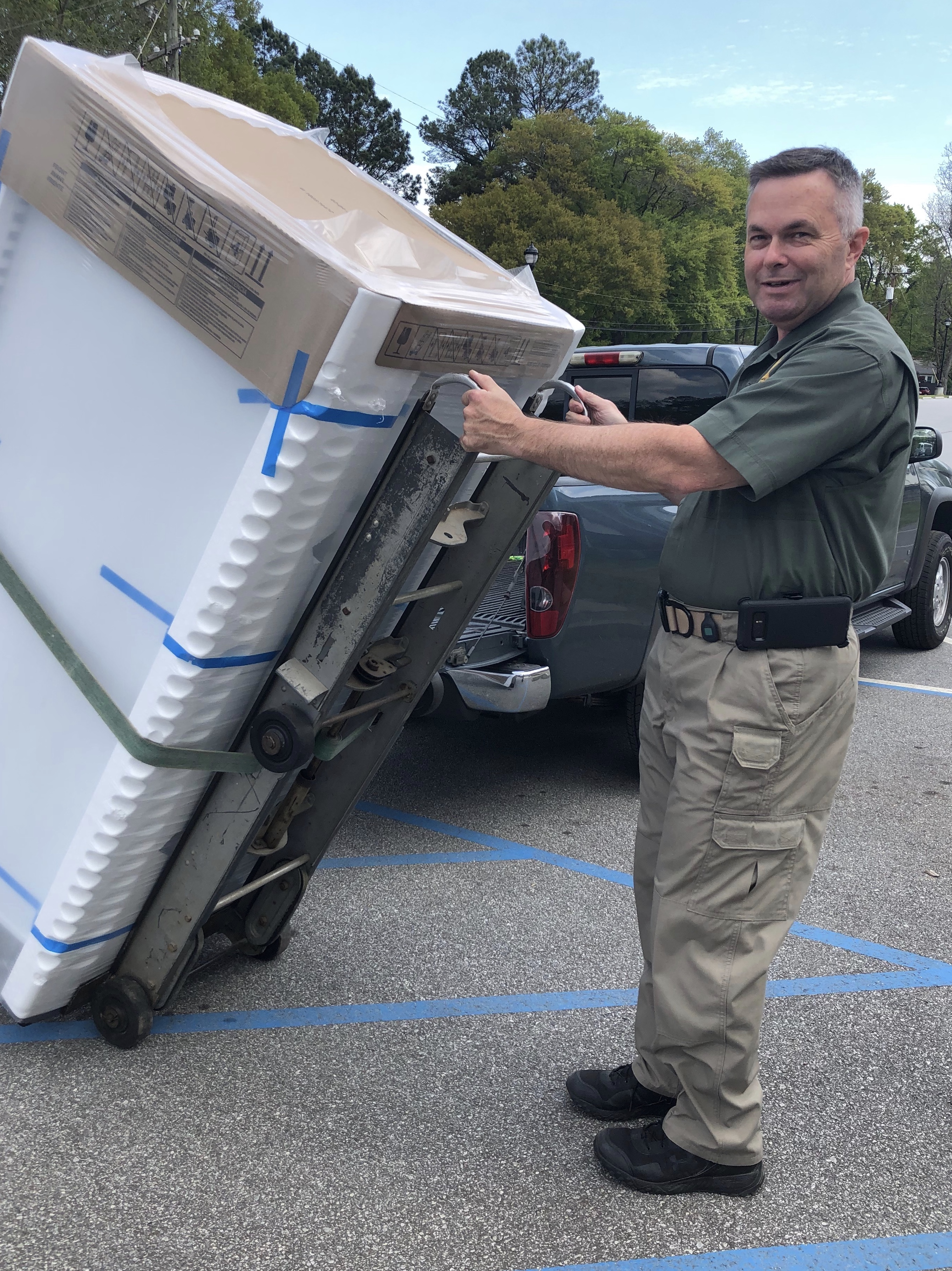 """Sheriff Rick Clark holds a newly purchased freezer on a moving dolly"""