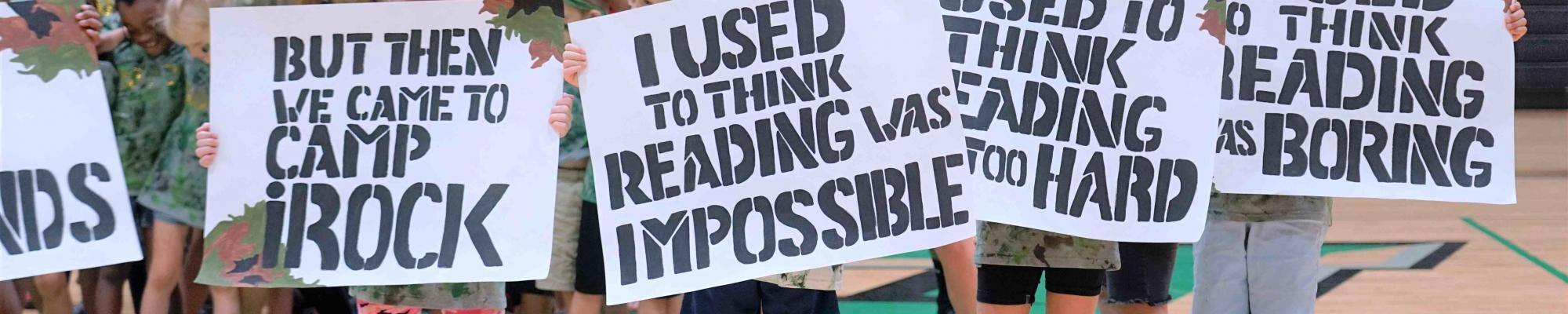 camp irock campers holding signs that say i used to think reading was impossible, but then i came to camp irock