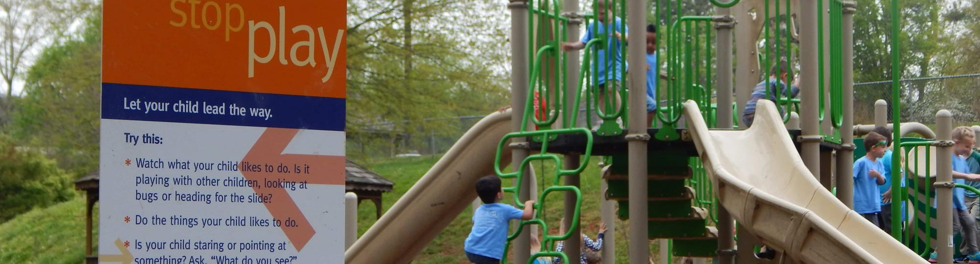 Children on a playground near a born learning trail sign