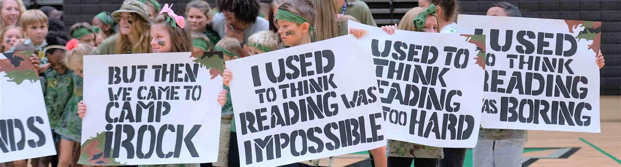 camp irock campers hold signs which say i used to think reading was impossible but then i came to camp irock
