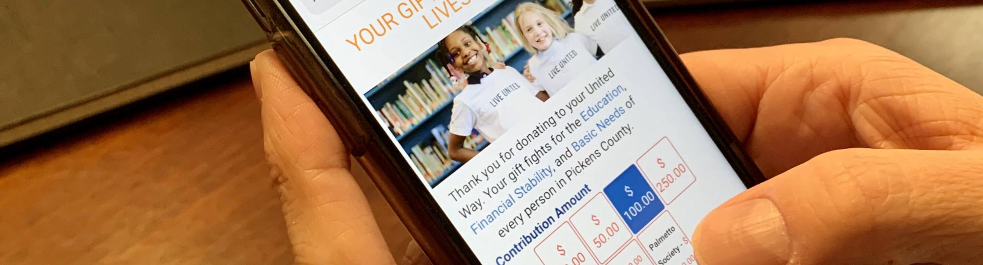 Person holding a phone opened to the donation page